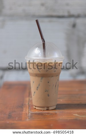 Iced coffee in take away cup (plastic glass) on the wood table in cafe #698505418