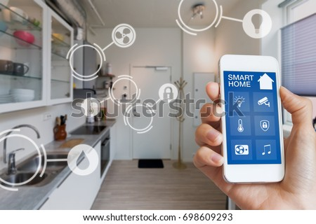 Smart home technology interface on smartphone app screen with augmented reality (AR) view of internet of things (IOT) connected objects in the apartment interior, person holding device #698609293