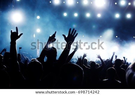 silhouettes of concert crowd in front of bright stage lights #698714242