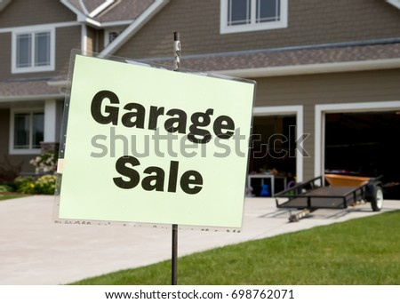 Garage sale sign on post in front of generic suburban garage