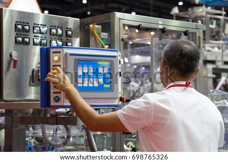 factory engineer controlling and pressing important technology button at control panel of an automatic machine in the manufacturing. Royalty-Free Stock Photo #698765326