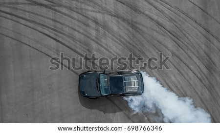 Aerial top professional driver drifting car on asphalt track, Black car tire drift skid mark on road race track, Black tire mark on street race track, Automobile and automotive concept. #698766346