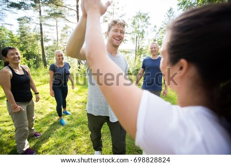 Man And Woman Giving High-Five While Friends Standing At Forest #698828824