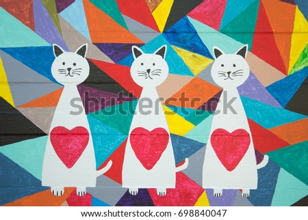 Three white cats on colorful abstract wood panel background