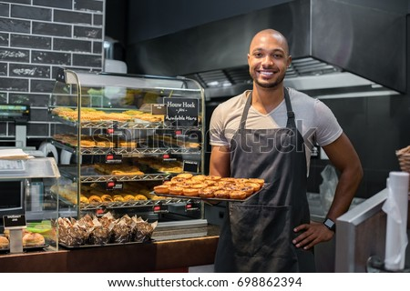 Smiling black baker with apron holding tray of small pastry and looking at camera. Young african chef holding sweet tray at cafeteria. Happy black man smiling at bakery. #698862394
