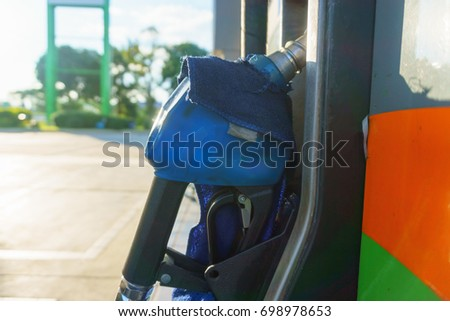 blue petrol pump nozzle for fill fuel at gas station in sunny day #698978653