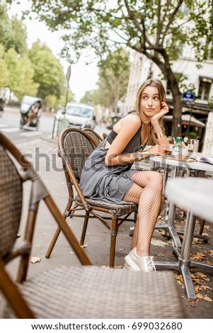 Portrait of a young and pretty woman in gray dress and cabaret tights sitting outdoors at the french cafe #699032680