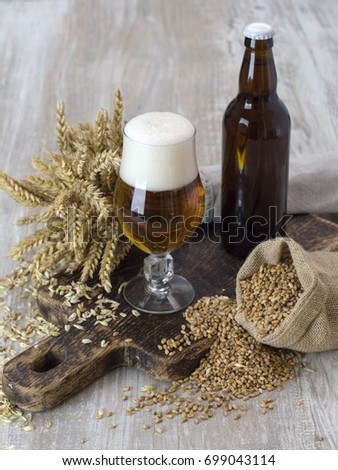 A glass of beer with wheat grains.  #699043114