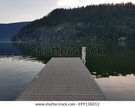 Dock On A Lake With Mountains in Background #699136012