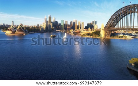Panorama of Sydney City CBD and Ferry to Manly in view of Circular Quay wharfs, high-rise business towers and Sydney Harbour bridge around Harbour. #699147379