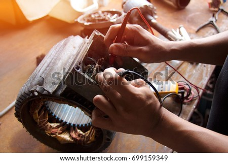Electrical Equipment Inspection :  Electricians use a standard multimeter tool :  Close up of electric motor maintenance work. Royalty-Free Stock Photo #699159349