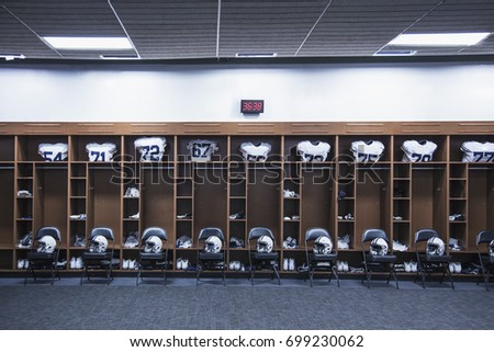 American Football locker room in a large stadium. Helmets sitting on chairs and jersey`s resting in the lockers #699230062