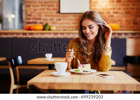 Gorgeous smiling young woman eating cake and drinking coffee at a cafeteria Royalty-Free Stock Photo #699239203