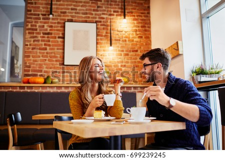 Couple of young people drinking coffee and eating cake in a stylish modern cafeteria Royalty-Free Stock Photo #699239245