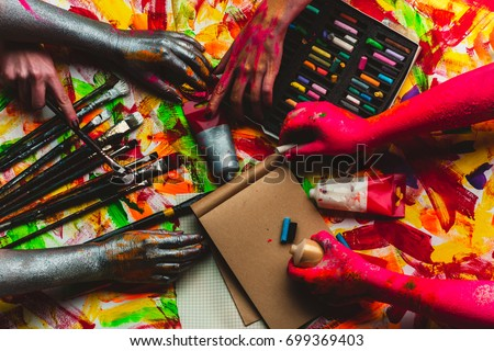 Hands, paint, art in art studio, colorful creative background. Red and silver hands paint picture on kraft paper. Modern art and art therapy, drawing lessons at school. Pastel pencils and watercolors