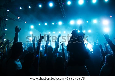 Concert crowd in front of bright stage lights. Silhouettes of people. #699370978