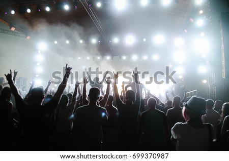 Concert crowd in front of bright stage lights. Silhouettes of people. #699370987