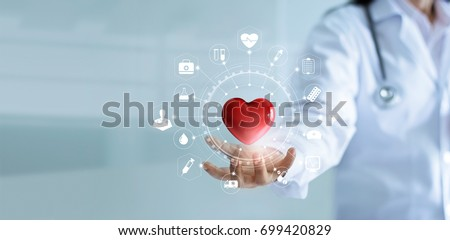 Medicine doctor holding red heart shape in hand with medical icon network connection modern virtual screen interface, service mind and medical technology network concept #699420829