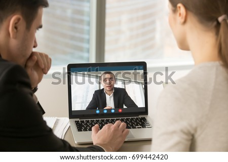 Employees participate virtual conference with boss running business remotely, businesspeople hold online meeting on laptop group chat, entrepreneurs making video call to partner, close up rear view #699442420