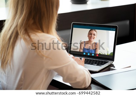 Two young women chatting online by making video call on laptop, using videoconferencing app for communication with distance friend, studying online course, virtual learning, close up rear view #699442582
