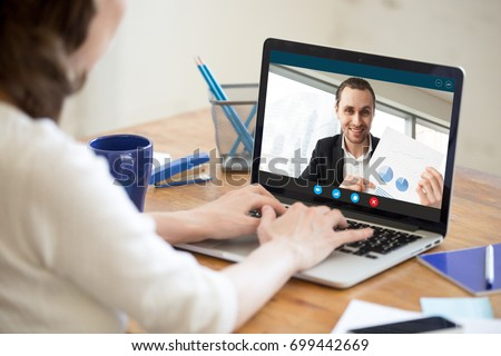 Businesswoman talking on video conference to businessman showing document at webcam, colleagues discussing work by video call application, financial consultant consulting client online, close up view #699442669