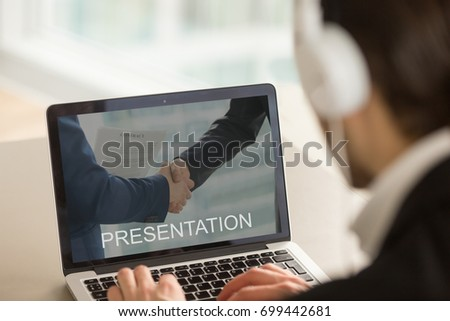 Businessman in headphones using pc, watching audio video computer business presentation, looking at laptop screen, office worker preparing slide show about startup company, close up rear view
