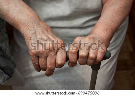 Elderly woman with walking stick at home #699475096
