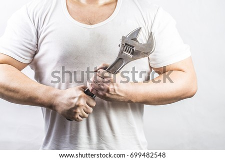 Man holding an adjustable wrench #699482548