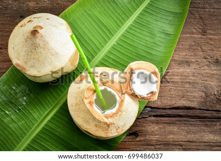 Two fresh coconut fruits ready to serve as beverage. Young coconut fruit cut open to drink sweet  juice and eat. Flat lay on green banana leaf and wood background.  #699486037