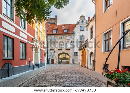 Narrow medieval street in old Riga that is the capital and largest city of Latvia, a major commercial, cultural, historical and tourist center of the Baltic region #699490750