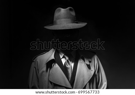 Man posing in the dark with a fedora hat and a trench coat, 1950s noir film style character Royalty-Free Stock Photo #699567733