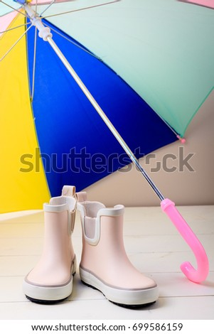 Pink little children rubber boots stand under colorful umbrella, concept of autumn or spring background. #699586159
