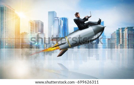 Fast internet concept with a businessman with laptop over a rocket #699626311