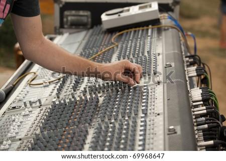 Hand on an audio mixer