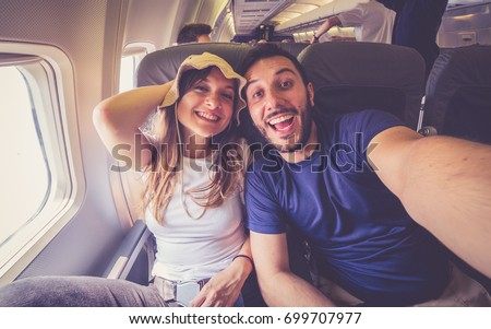 Young handsome couple taking a selfie on the airplane during flight around the world. They are a man and a woman, smiling and looking at camera. Travel, happiness and lifestyle concepts. Royalty-Free Stock Photo #699707977