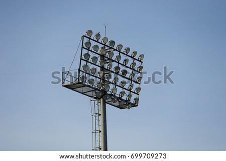 Stadium floodlight with metal pole with blue sky in the football stadium. #699709273