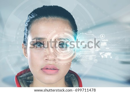 Close up of a futuristic woman looking at virtual graphics on her eyes #699711478