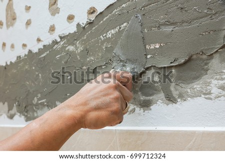 craftman hand using trowel plastering cement mortar wall #699712324