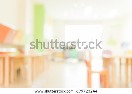 School classroom in blur background without young student; Blurry view of elementary class room no kid or teacher with chairs and tables in campus. Vintage effect style pictures.