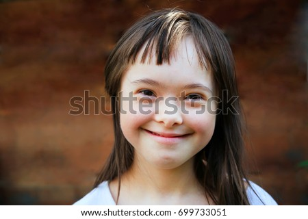 Cute smiling down syndrome girl on the brown background Royalty-Free Stock Photo #699733051