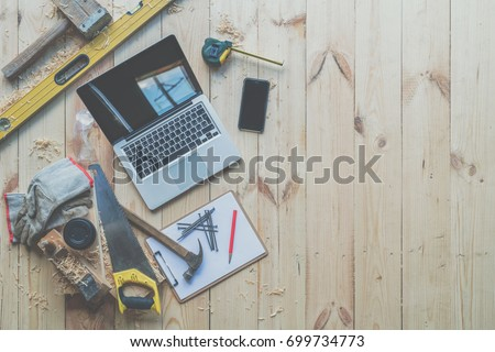 Background. Top view. On wooden planks laptop, smartphone, clipboard with empty white sheet, nails, hammer, saw, tape measure, level, gloves, glasses and cup of coffee.Construction, carpentry. Mock up #699734773