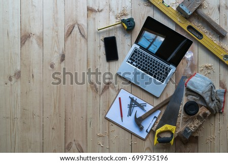 Background. Top view. On wooden planks laptop, smartphone, clipboard with empty white sheet, nails, hammer, saw, tape measure, level, gloves, glasses and cup of coffee,sawdust.Construction, carpentry. #699735196