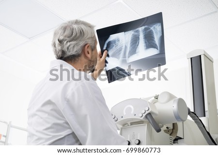 Male Doctor Analyzing Chest X-ray In Examination Room Royalty-Free Stock Photo #699860773