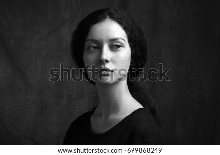 Dramatic black and white portrait of a beautiful lonely girl with freckles isolated on a dark background in studio shot #699868249