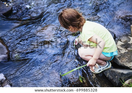 Adorable little child girl playing and having fun by leaves near mountain river on warm and sunny summer day. (Holiday, rest, happy childhood, games, nature concept) #699885328