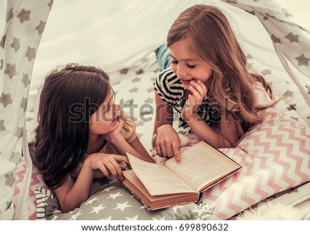 Two cute little girls are reading a book and smiling while playing together in child's teepee #699890632
