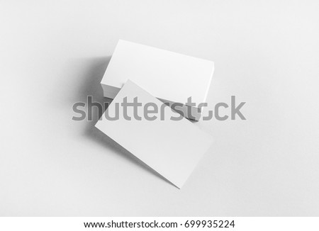 Blank business cards on paper background. Mockup for branding identity. Studio shot.