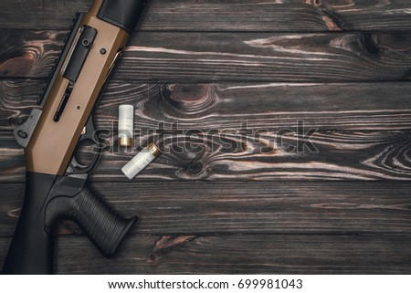 Black silver shotgun on a wooden background #699981043