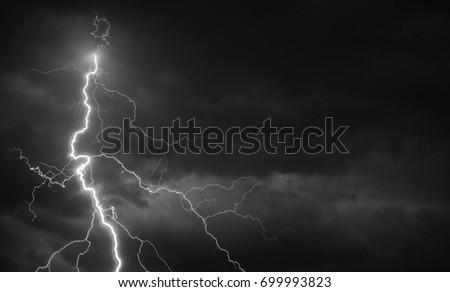 Fork lightning striking down during summer storm in black and white.