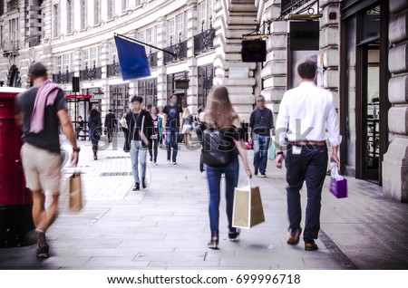 Anonymous shoppers walking down busy London shopping street #699996718